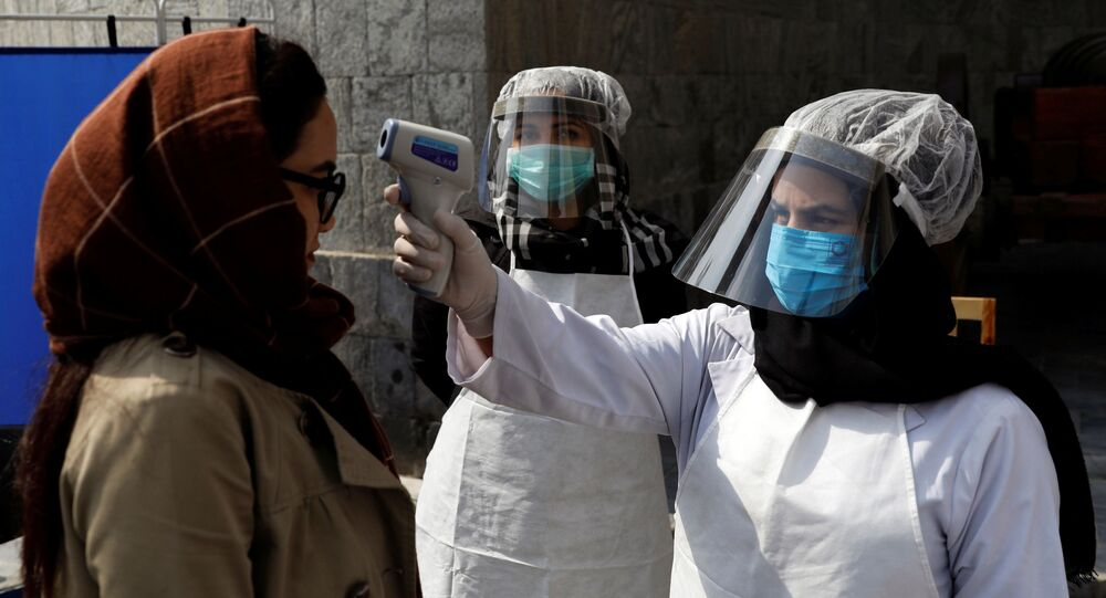 Afghan health worker in protective gear checks the temperature of a woman