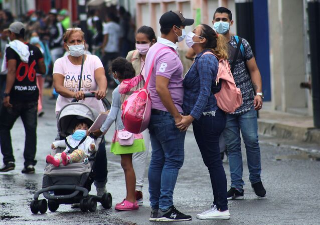 People wear face masks near the Venezuelan-Colombia border after the Colombian government decided to close the Simon Bolivar international bridge as a preventive measure in response to the spreading coronavirus disease (COVID-19) in San Antonio, Tachira, Venezuela