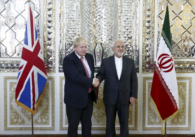 Iranian Foreign Minister Mohammad Javad Zarif, right, and his British counterpart Boris Johnson, shake hands as they pose for media prior to talks in Tehran, Iran, Saturday, Dec. 9, 2017