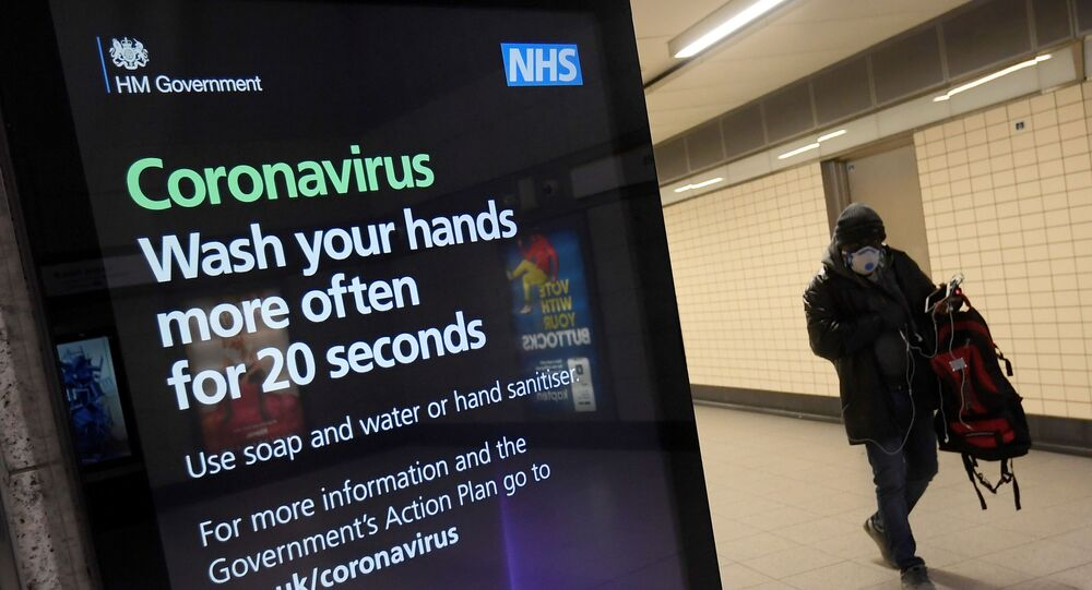 A man in a protective face mask walks past a British government public health campaign advertisement at Victoria underground station