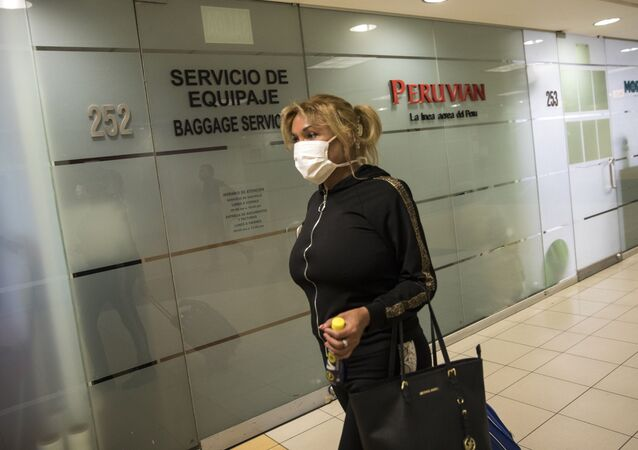 Protected with a mask, a passenger walks to the departure lounge at the international airport in Lima, Peru, Friday, 6 March 2020. On Friday, Peruvian President Martin Vizcarra announced the first case of the new coronavirus in the country