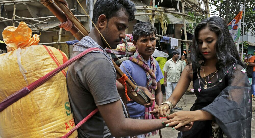 An Indian sex worker, right, ties a rakhi or a sacred thread on the wrist of a commuter as a symbolic gesture during Raksha Bandhan festival inside Sonagachhi, the biggest red light district in Kolkata, India, Monday, Aug. 7, 2017