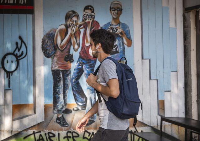 A man wears a face mask as he walks along a main street in Tel Aviv, Israel, Sunday, March 15, 2020