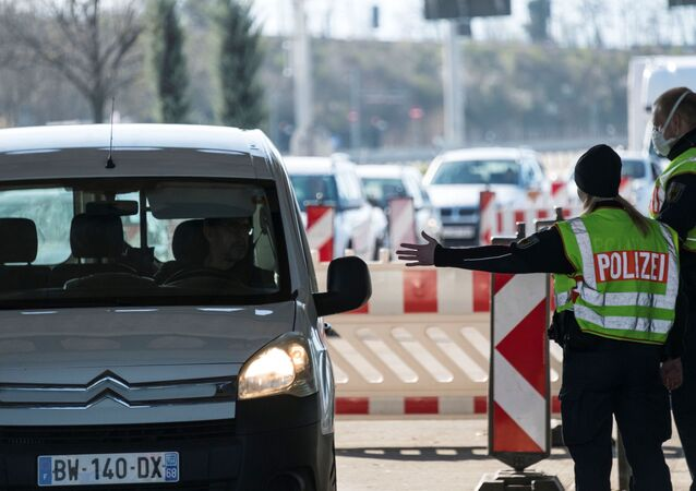 German policemen control motorists trying to cross the Swiss-German border on 16 March 2020, in Weil am Rhein near Basel. - Germany  has reintroduced border controls with France, Austria, Switzerland, Luxemburg and Denmark from March 16, 2020 due to the coronavirus crisis, interior minister Horst Seehofer said the day before.
