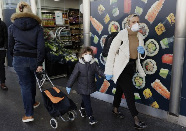 A woman and her daughter wear masks and gloves as they pass a shop in London on 16 March 2020.