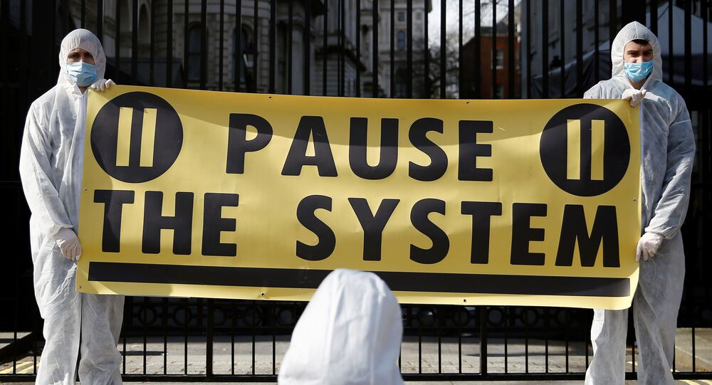 Protesters from organization Pause the System wearing hazmat suits demonstrate against government's response to the coronavirus crisis, outside Downing Street in London, Britain March 16, 2020. REUTERS/Henry Nicholls