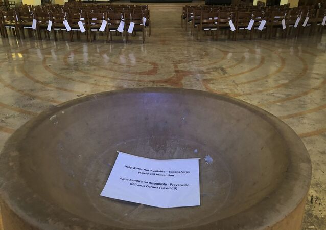 In this Saturday, March 14, 2020 photo, a sign reads, Holy Water Not Available in the baptismal font of the St. Stephen and the Incarnation Episcopal Church in Washington, which is closed due to the coronavirus pandemic.