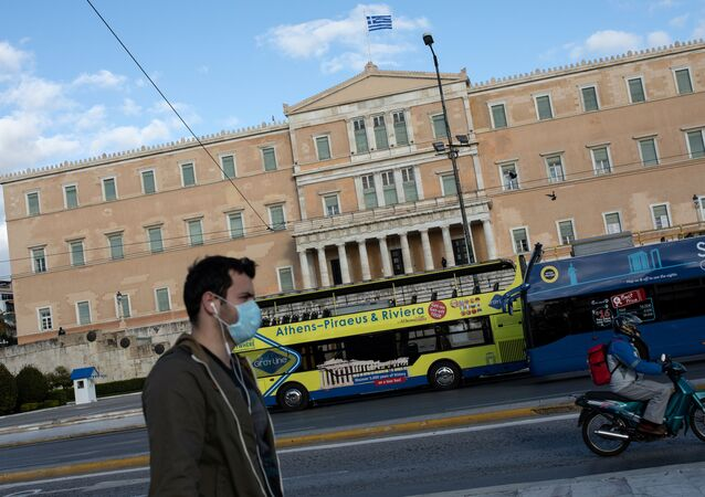 A man wearing a protective face mask walks past the parliament building in Athens, Greece