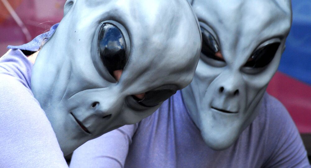 Two aliens pose for a photograph in front of Imagine That Scrapbooks on Main Street in downtown Roswell, N.M., Friday, July 6, 2007, during the UFO Festival
