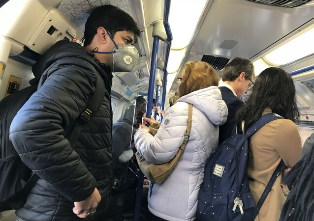 A traveller wears a mask on a busy underground train in London amid fears of the coronavirus outbreak