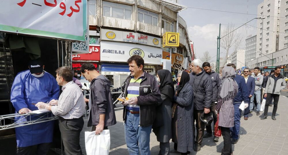 People queue in line to receive packages for precautions against COVID-19 coronavirus disease provided by the Basij, a militia loyal to Iran's Islamic republic establishment, from a booth outside Meydane Valiasr metro station in the capital Tehran on March 15, 2020. - Iran on March 15 announced that the new coronavirus has killed 113 more people, the highest single-day death toll yet in one of the world's worst-affected countries.