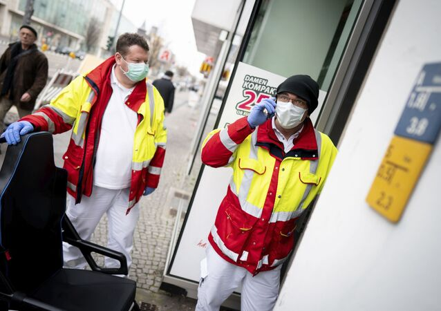 Paramedics from a patient transport company wearing face masks and gloves as they stand at the entrance to an apartment building to pick up a patient in the district Steglitz in Berlin, Germany, March 17, 2020