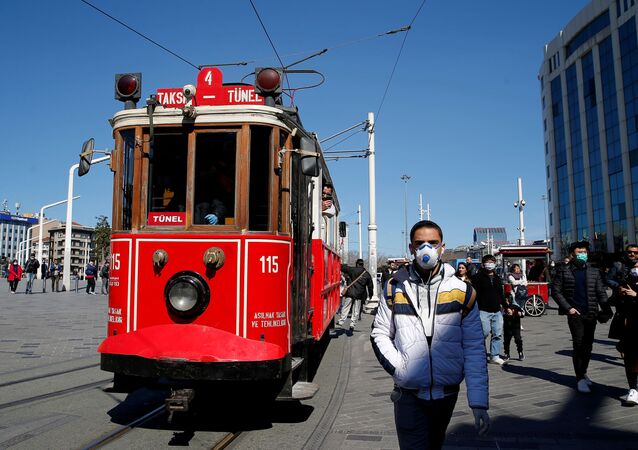 People wearing protective face masks, due to coronavirus disease (COVID-19) concerns, walk at Taksim square in central Istanbul, Turkey, March 17, 2020