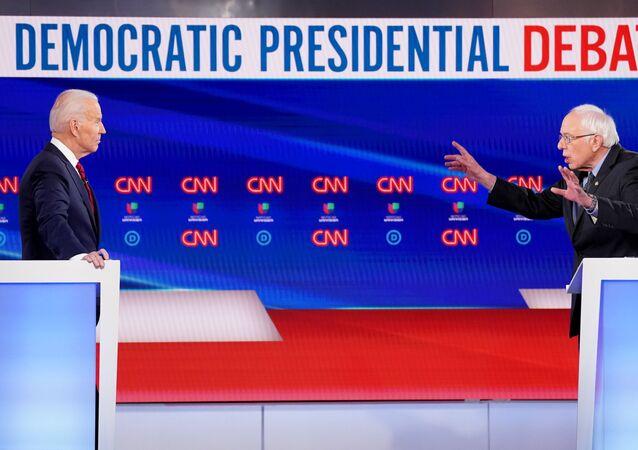 Democratic U.S. presidential candidate and former Vice President Joe Biden listens as Senator Bernie Sanders speaks during the 11th Democratic candidates debate of the 2020 U.S. presidential campaign