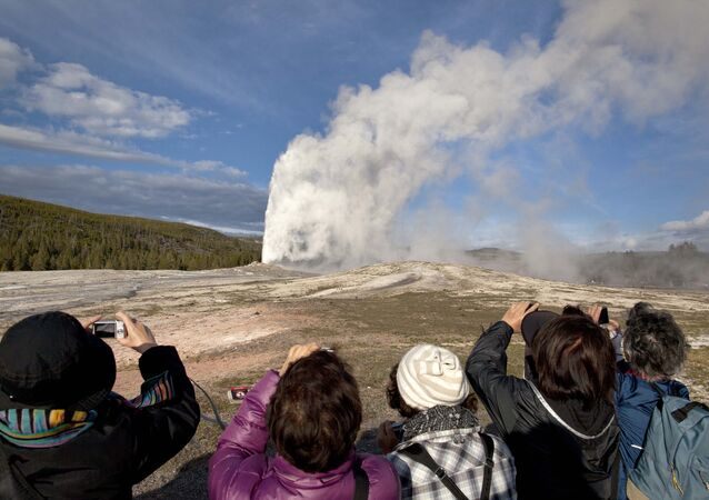FILE - In this May 21, 2011 file photo, tourists photograph Old Faithful erupting, at Yellowstone National Park, in Mont. Old Faithful is among the park's hydrothermal  features powered by the Yellowstone supervolcano. Scientists have discovered a  new, deeper reservoir of partly molten rock beneath the Yellowstone supervolcano. But they said the find doesn't change the chances of a volcanic eruption. (AP Photo/Julie Jacobson,File)