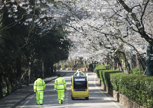 Security personnel walk next to a 5G enabled autonomous vehicle, installed with a camera filming blooming cherry blossoms for an online live-streaming session, inside the closed Wuhan University, in Wuhan, China, March 17, 2020