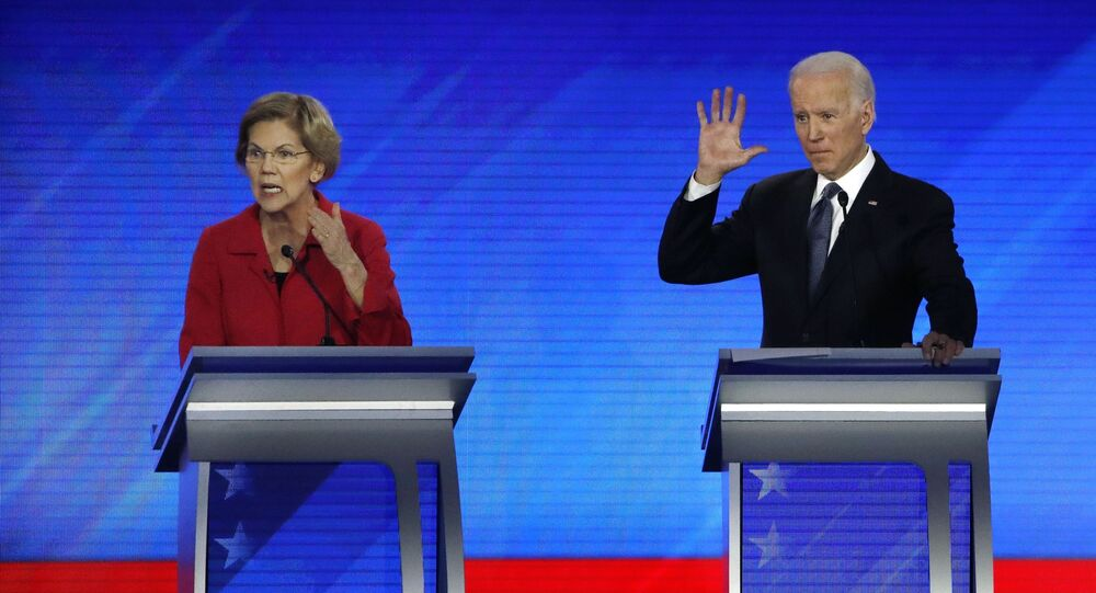 Democratic presidential candidate Sen. Elizabeth Warren, D-Mass., left, speaks as former Vice President Joe Biden waits during a Democratic presidential primary debate, Friday, Feb. 7, 2020, hosted by ABC News, Apple News, and WMUR-TV at Saint Anselm College in Manchester, N.H.