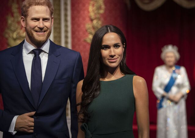 The figures of Britain's Prince Harry and Meghan, Duchess of Sussex, left, are moved from their original positions next to Queen Elizabeth II, Prince Philip and Prince William and Kate, Duchess of Cambridge, at Madame Tussauds in London, Thursday Jan. 9, 2020