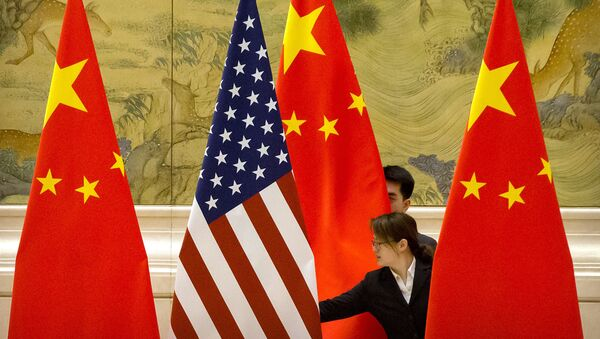 FILE - In this Feb. 14, 2019, file photo, Chinese staffers adjust U.S. and Chinese flags before the opening session of trade negotiations between U.S. and Chinese trade representatives at the Diaoyutai State Guesthouse in Beijing. Beijing on Friday, June 28, 2019 - Sputnik International