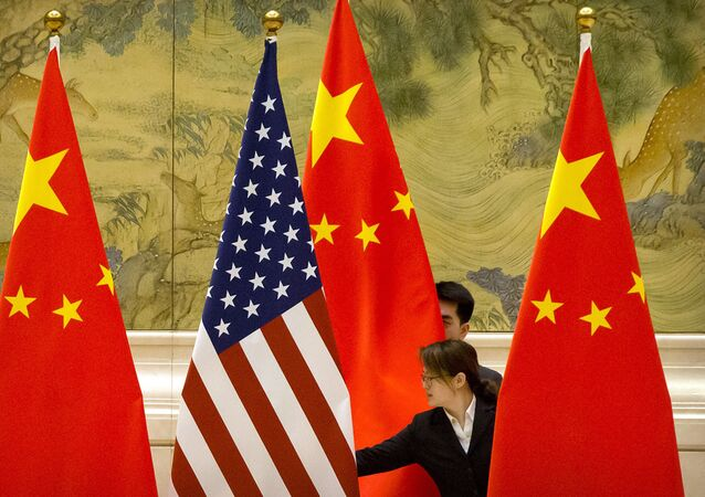 FILE - In this Feb. 14, 2019, file photo, Chinese staffers adjust U.S. and Chinese flags before the opening session of trade negotiations between U.S. and Chinese trade representatives at the Diaoyutai State Guesthouse in Beijing. Beijing on Friday, June 28, 2019