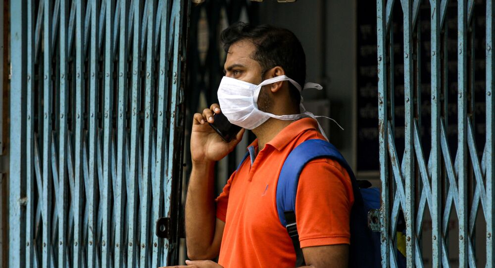 An Indian man wearing a mask talks on his mobile phone at a government run hospital where a special ward has been set aside for possible COVID-19 patients in Kolkata, India, Friday, March 6, 2020