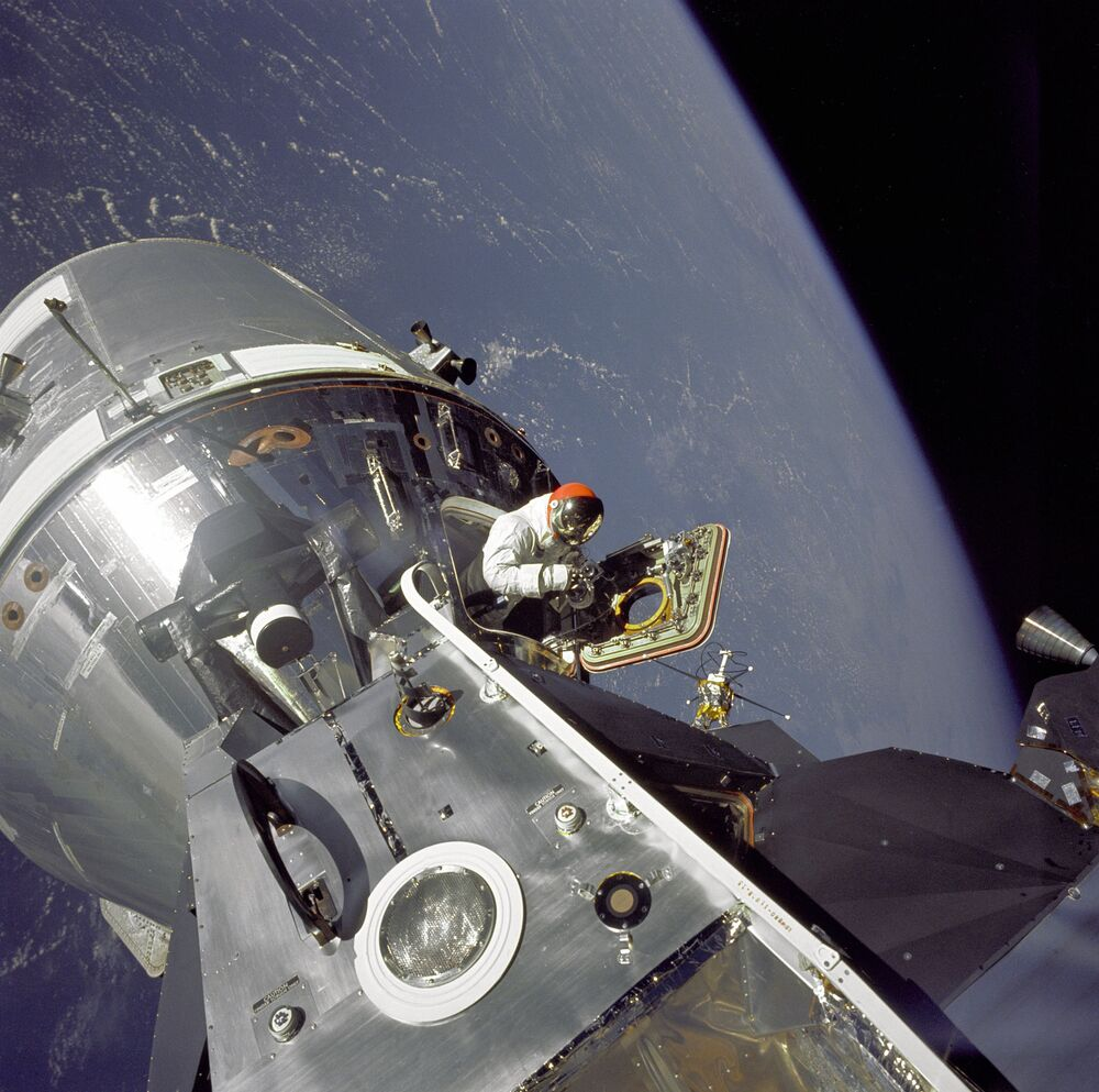 Gumdrop meets Spider. Apollo 9 Command/Service Modules (CSM) nicknamed Gumdrop, and Lunar Module (LM), nicknamed Spider, are shown docked together as Command Module pilot David R. Scott stands in the open hatch. Astronaut Russell L. Schweickart, Lunar Module pilot, took this photograph of Scott as he stood on the porch outside the Lunar Module, 6 March 1969.