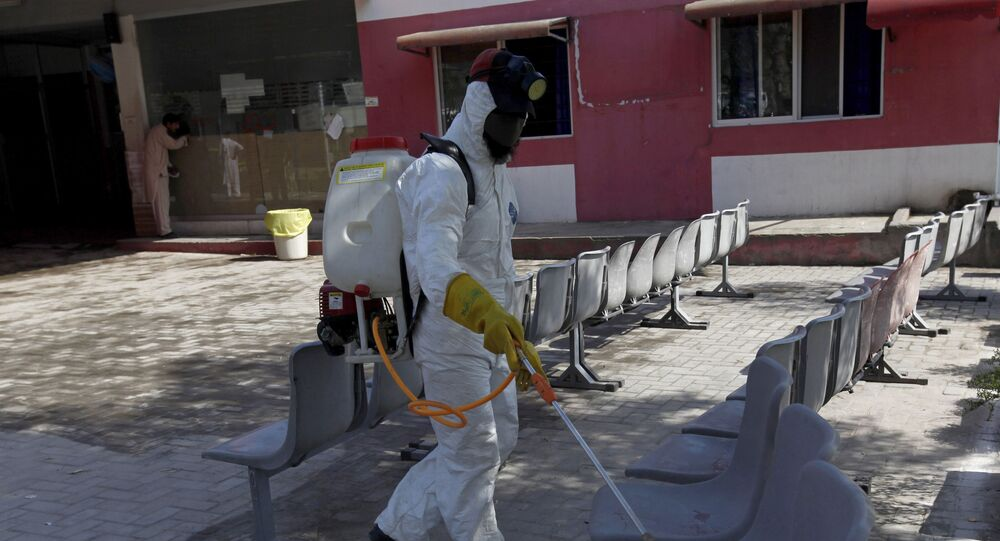 A worker wearing protective gear sprays disinfectant as a precaution against the new coronavirus, at the Pakistan Institute of Medical Sciences Hospital, in Islamabad, Pakistan, Tuesday, March 17, 2020.