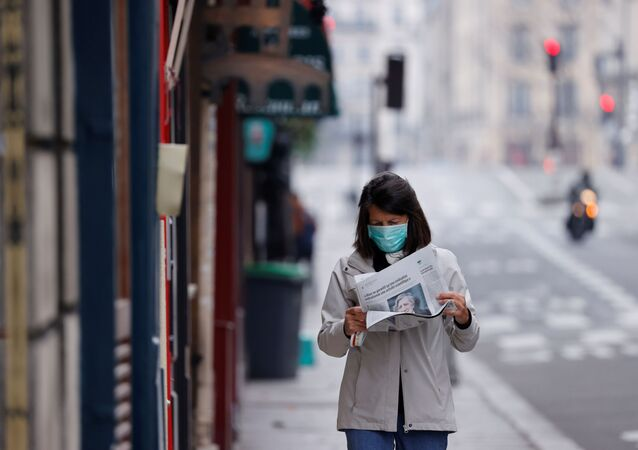A woman wearing a protective face mask reads a newspaper as she walks in a street on the deserted Ile Saint Louis in Paris as lockdown is imposed to slow the rate of the coronavirus disease (COVID-19) in France, March 18, 2020.