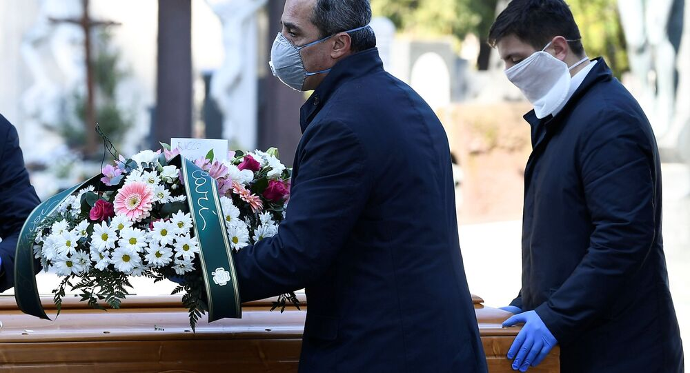Cemetery workers and funeral agency workers in protective masks transport a coffin of a person who died from coronavirus disease (COVID-19), into a cemetery in Bergamo, Italy March 16, 2020