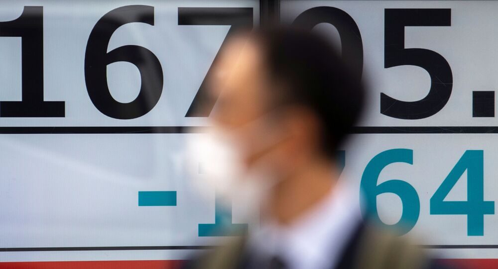 A man wearing a protective face mask, following an outbreak of coronavirus (COVID-19), walks past a screen showing the Nikkei index outside a brokerage in Tokyo, Japan, March 13, 2020
