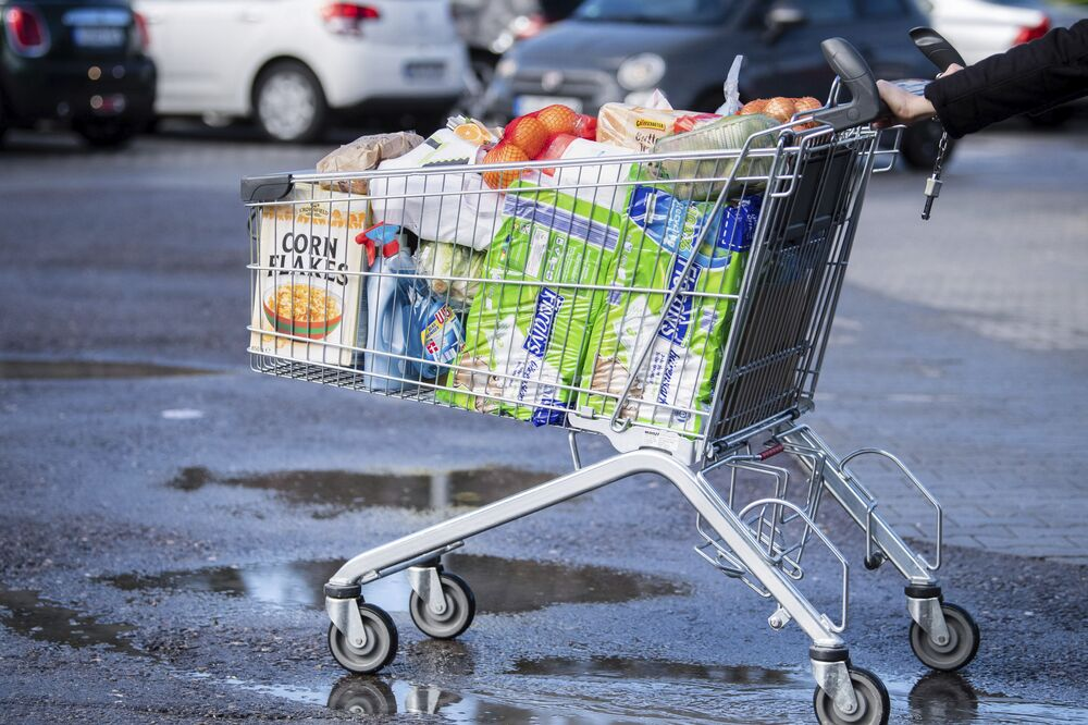 A customer pushes a shopping trolley filled to the brim across the parking lot of a supermarket in Pullach, Germany, Friday, March 13, 2020. For most people, the new coronavirus causes only mild or moderate symptoms, such as fever and cough. For some, especially older adults and people with existing health problems, it can cause more severe illness, including pneumonia.