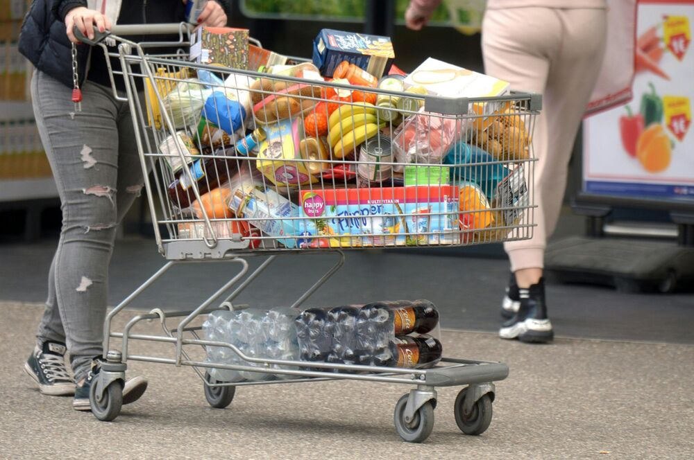 A person pushes a full shopping cart with various groceries on March 13, 2020, in Stockerau in Tyrol, Austria.