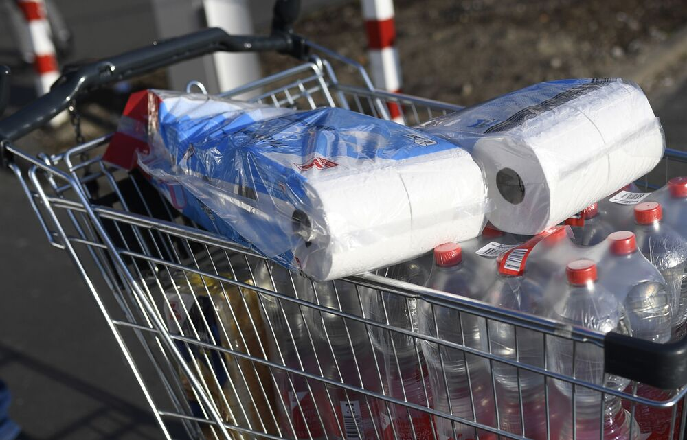 A picture taken on photo on March 16, 2020 shows a shopping cart with toilet paper and mineral water at a supermarket in Dortmund, where activities came to a halt due to the novel coronavirus.