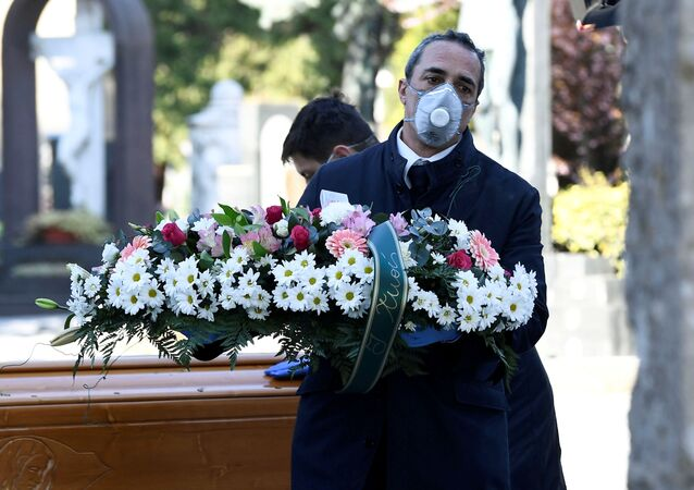 Cemetery workers and funeral agency workers in protective masks transport a coffin of a person who died from coronavirus disease (COVID-19), into a cemetery in Bergamo, Italy March 16, 2020.