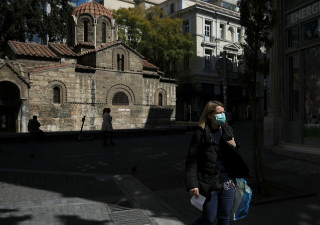 A woman wears a protective face mask as she walks next to a church in Athens, Greece, March 17, 2020.