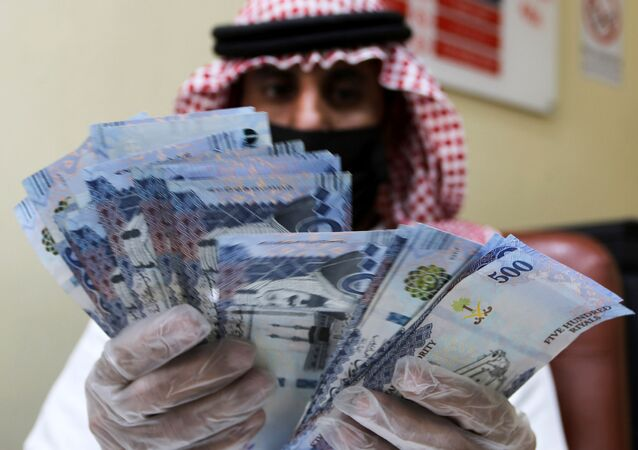 A Saudi money exchanger wears gloves as he counts Saudi riyal currency at a currency exchange shop in Riyadh, Saudi Arabia March 10, 2020