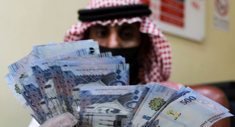 A Saudi money exchanger wears gloves as he counts Saudi riyal currency at a currency exchange shop in Riyadh, Saudi Arabia March 10, 2020