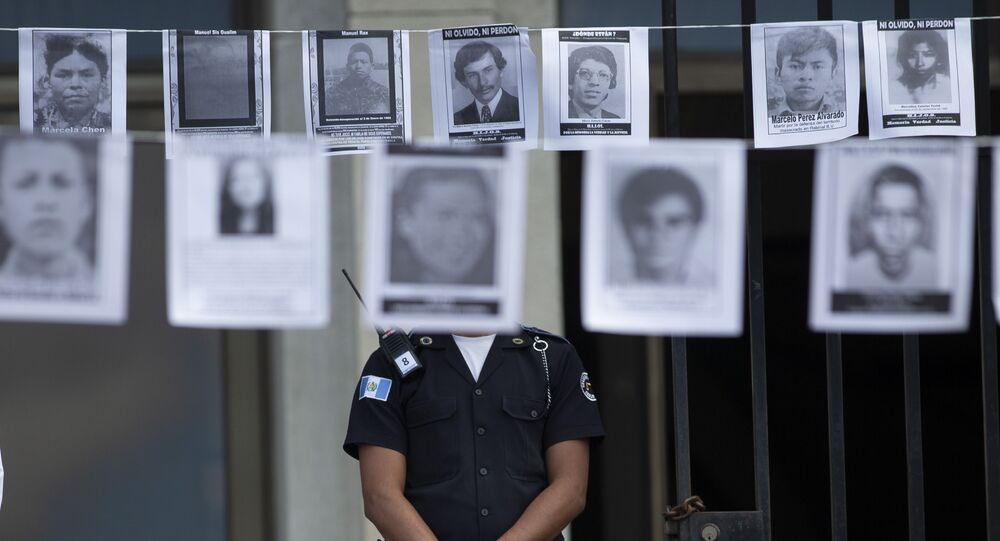A police officer stands guard outside the Supreme Court, below photos of people who were forcibly disappeared between 1978 and 1982
