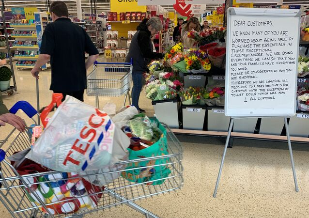 A customer walks past a sign informing shoppers about limited stock inside a Tesco supermarket, during the coronavirus disease (COVID-19) outbreak, in Liverpool, Britain, March 18, 2020.