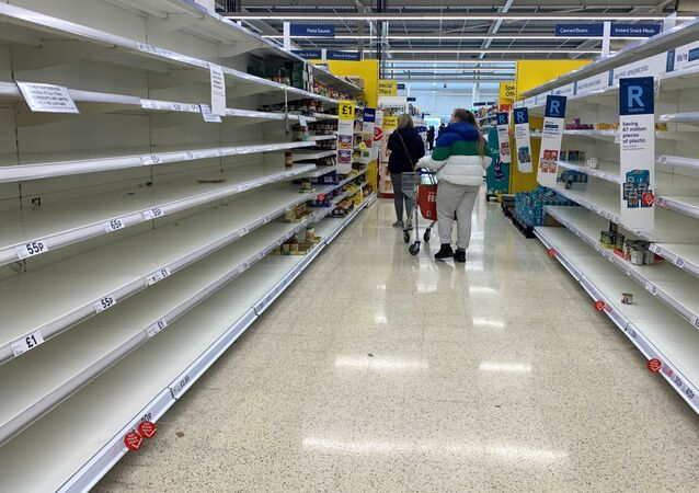 Shoppers walk past empty shelves inside a Tesco supermarket, during the coronavirus disease (COVID-19) outbreak, in Liverpool, Britain, March 18, 2020.