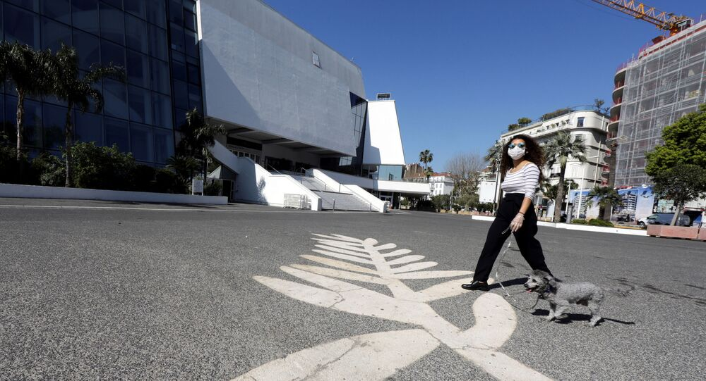 A woman wearing a protective face mask near the Festival palace on the Croisette in Cannes