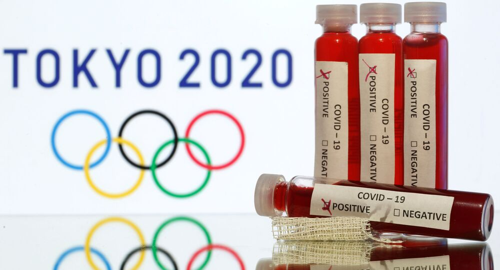 Fake blood in seen in test tubes labelled with coronavirus disease (COVID-19) in front of a displayed Tokyo 2020 Olympics logo in this illustration taken March 19, 2020