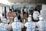 Passengers register their information at the New China International Exhibition Center, a transit hub to screen incoming passengers from the Beijing Capital International Airport for COVID-19, caused by the coronavirus, in Beijing, China March 18, 2020. Picture taken March 18, 2020