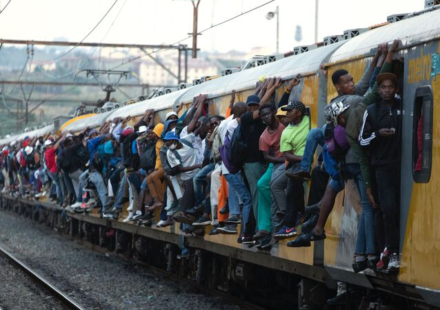Train commuters hold on to the side of an overcrowded passenger train in Soweto, South Africa, Monday, March 16, 2020.