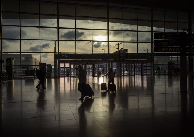 Passengers walk in an empty terminal at the airport of Barcelona, Spain, Thursday, March 19, 2020