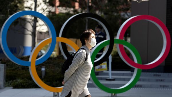 FILE PHOTO: A woman wearing a protective face mask, following an outbreak of the coronavirus disease (COVID-19), walks past the Olympic rings in front of the Japan Olympics Museum in Tokyo, Japan March 13, 2020 - Sputnik International