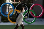 FILE PHOTO: A woman wearing a protective face mask, following an outbreak of the coronavirus disease (COVID-19), walks past the Olympic rings in front of the Japan Olympics Museum in Tokyo, Japan March 13, 2020