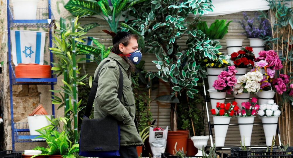 A man wears a face mask as he walks in a market in Ashkelon while Israel tightened a national stay-at-home policy following the spread of coronavirus disease (COVID-19) in Ashkelon, Israel March 20, 2020