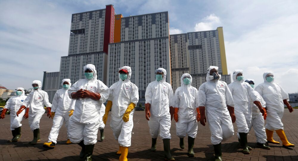 Indonesian Red Cross Society personnel walk in protective suits during an operation to spray disinfectant at the Kemayoran Athletes Village, to prevent the spread of coronavirus disease (COVID-19) in Jakarta, Indonesia, March 21, 2020.
