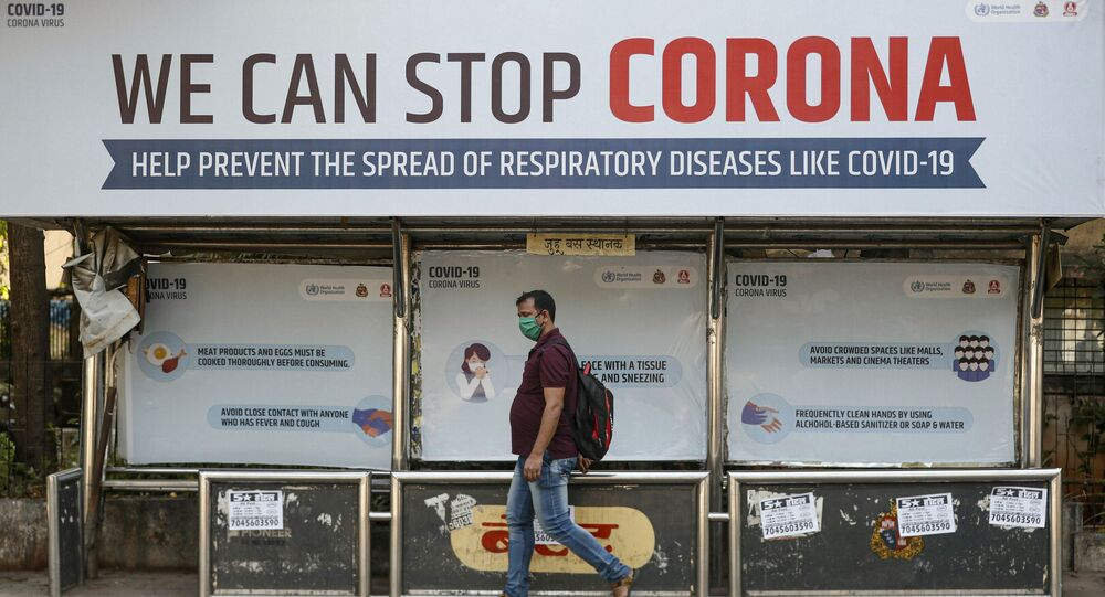 FILE PHOTO: A man wearing a protective mask walks past a bus stop displaying preventive measures against the coronavirus in Mumbai, India, March 18, 2020.
